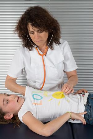 pediatra: Pediatra femenina examinar la respiraci�n un poco de las ni�as