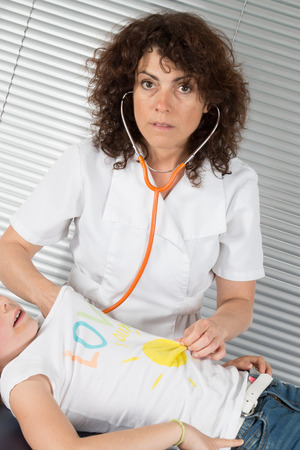 examining: Female pediatrician examining a little girls breathing Stock Photo