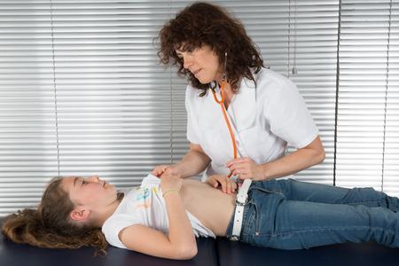 pediatra: Pediatra femenina examinar la respiración un poco de las niñas