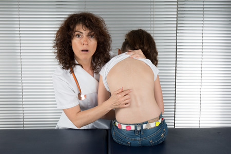 female doctor examines the back of  young girl