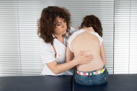 listening back: female doctor examines the back of  young girl