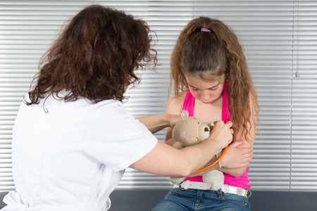 angry teddy: Female doctor tries to examine unhappy young girl