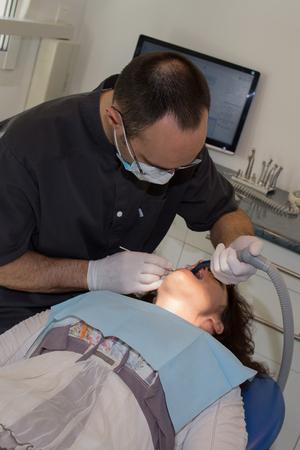 examined: Woman having teeth examined at dentists