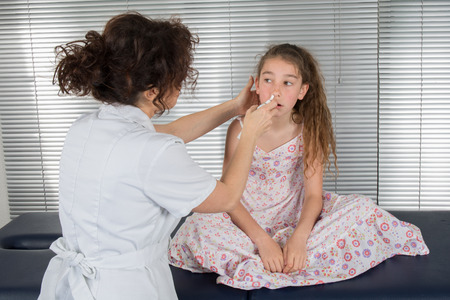 auscultation: Auscultation, young girl doctor tries to clean her noise Stock Photo