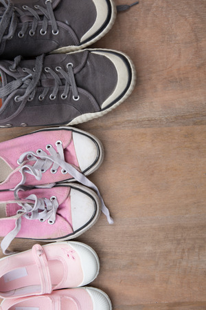 Family shoes on wooden background, family concept