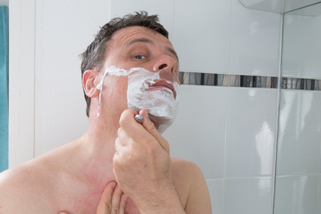 aftershave: Man shaving with a razor blade and shaving cream in bathroom Stock Photo