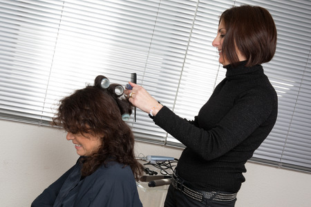 combing: Hairstylist combing  client in hairdressing salon