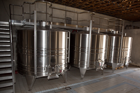 vats: Stainless steel wine vats in a row inside the winery Stock Photo
