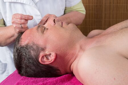 female large intestine: Acupuncturist prepares to tap needle around face  of man