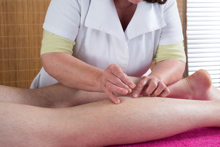 acupuncturist: Woman acupuncturist prepares to tap needle on scarf of a man Stock Photo