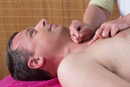 acupuncturist: Acupuncturist prepares to tap needle on mans torso