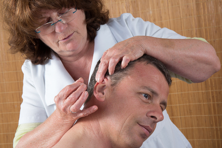 female large intestine: Woman acupuncturist prepares to tap needle around ears of man Stock Photo