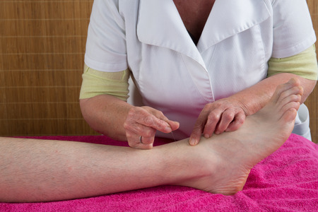 female large intestine: Acupuncturist prepares to tap needle on the foot of a man Stock Photo