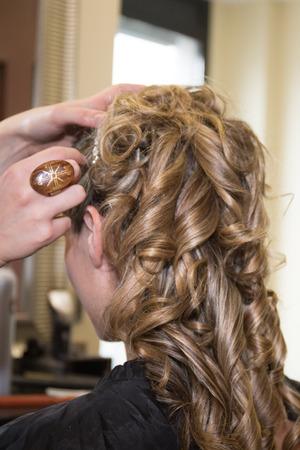 Smiling Young woman hairdo at hairdressing salon doing a bun photo