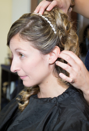 catfight: Smiling Young woman hairdo at hairdressing salon doing a bun Stock Photo