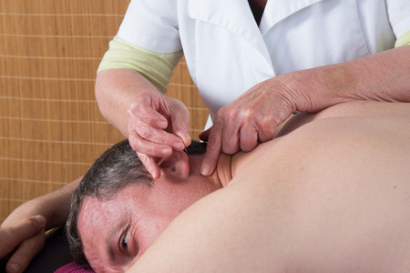 female large intestine: Woman acupuncturist prepares to tap needle into ears of man