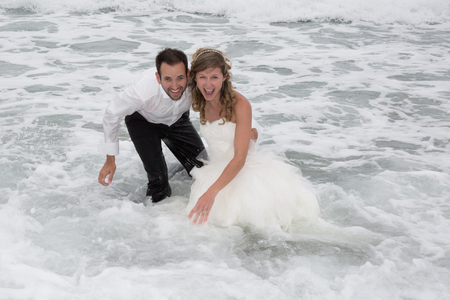 ocea: Lovely and Happy newlywed couple standing in water. Stock Photo