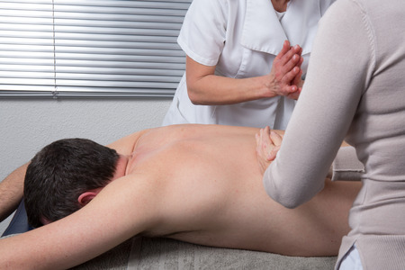 massage therapy: The massage with 4 hands Stock Photo