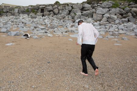 Wet water man on the beach with trousers and shirt photo