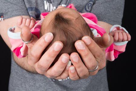 cradling: Newborn baby Sleeping on father hands on Black  Stock Photo