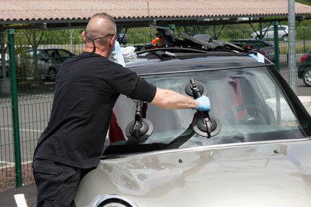 glazier: Glazier removing windshield or windscreen on a car