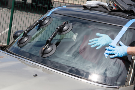 replacement: Glazier removing windshield or windscreen on a car
