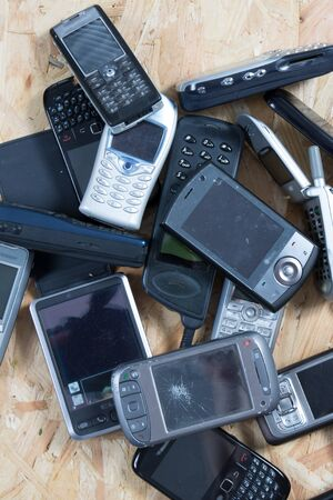 Old and obsolete cellphone on wooden background photo