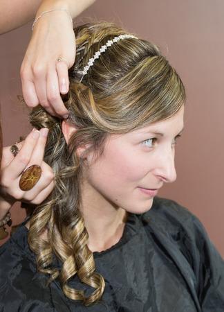 chignon: Smiling Young woman hairdo at hairdressing salon doing a bun Stock Photo