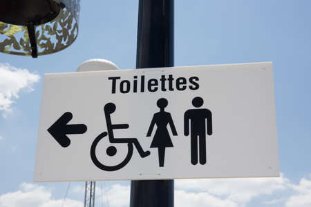 latrine: Restroom icon, toilette signs under blue sky with clouds Stock Photo