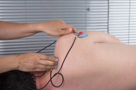 orthopaedic: Orthopaedic treatment electrostimulator. Electrodes of the girl in neck. Stock Photo