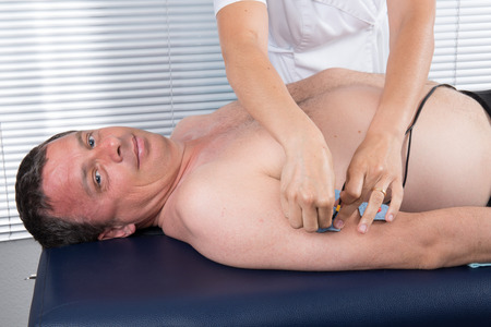 body toning: Man getting an  electric massage on his arm