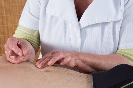 acupuncturist: Acupuncturist prepares to tap needle on the belly of a man