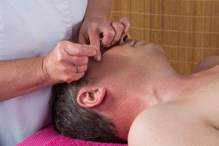 acupuncturist: Acupuncturist prepares to tap needle around face  of man