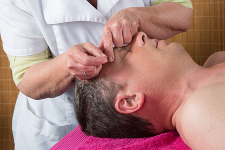 ear acupuncture: Acupuncturist prepares to tap needle around face  of man