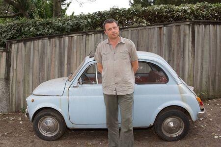 L'homme est en attente pour quelqu'un en face d'une petite voiture de collection
