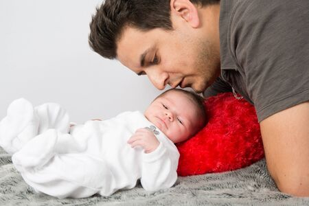 cuddling: Loving father cuddling his new born baby