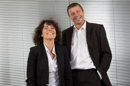 confidently: Successful business partners with a man and woman  smiling confidently at the camera Stock Photo