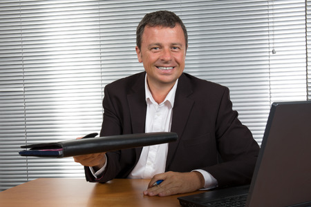 40 year old man: Charming man at office looks happy and satisfied
