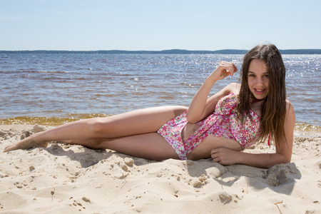 Teenager, girl in pink swimming suit on the beach