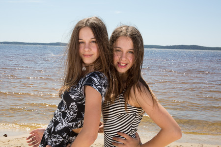 Pretty Twin teenage girls playing at the beach