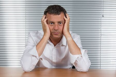 worried businessman: Worried businessman holding his head in his office