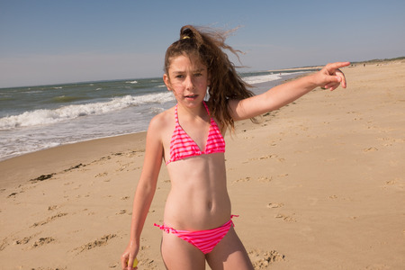 Young girl is pointing her finger to the ocean