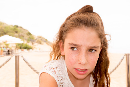 10 11 years: Close up portrait of a ten year old girl, smiling up at the camera. Positive emotion Stock Photo