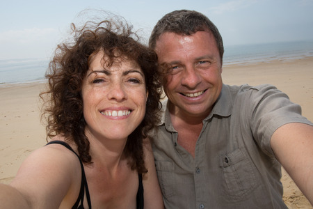 taking a wife: Man and  woman caucasian couple, taking vacation selfie photograph at the beach