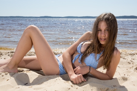 Teenager, girl in blue swimming suit on the beach Standard-Bild