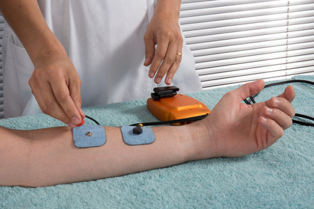 medical procedure: Man is doing massage of electrostimulator Medical procedure.