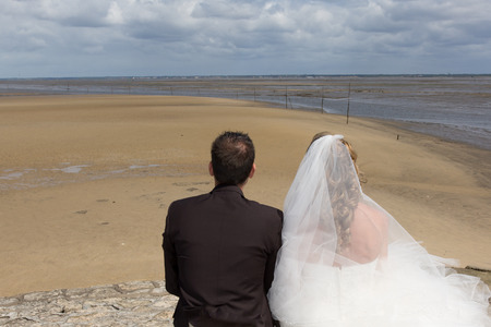 newly wedded couple: Beautiful couple on the beach in wedding dress