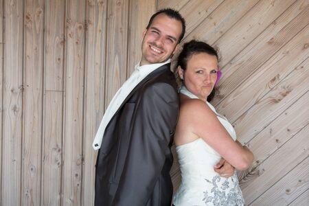 matrimonio feliz: Pares de la boda espalda con espalda bajo el fondo de madera