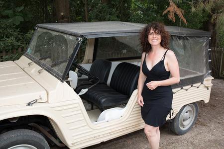 Woman with a black dress close to a beach car, mehari Stock Photo