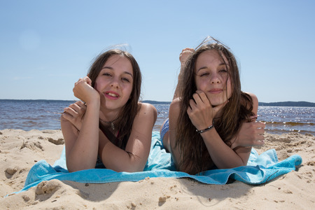 complicity: Complicity of two sisters on the beach Stock Photo